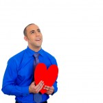 Man looking upwards, holding red heart to chest daydreaming of women in love